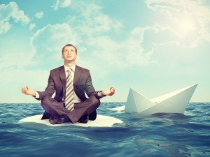 Businessman sitting in lotus position on small island in sea and looking up, sinking paper boat on right side